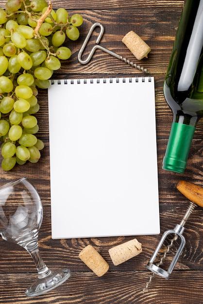 Бутылка вина и виноград рядом с блокнотом Бесплатные Фотографии