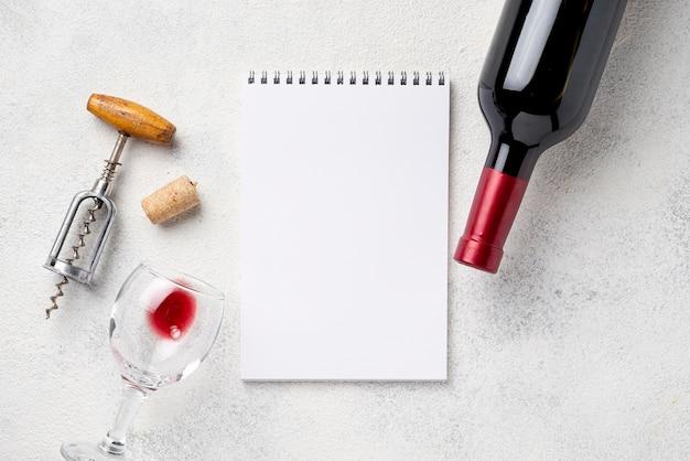ワインのボトルとグラスの横にあるノート 無料写真