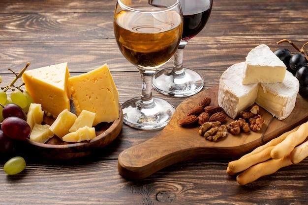 ワインの試飲のためのさまざまなチーズが入った木製トレイ 無料写真