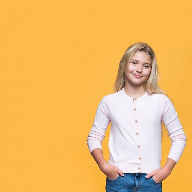 黄色の背景を持つ正面若い女の子 無料写真