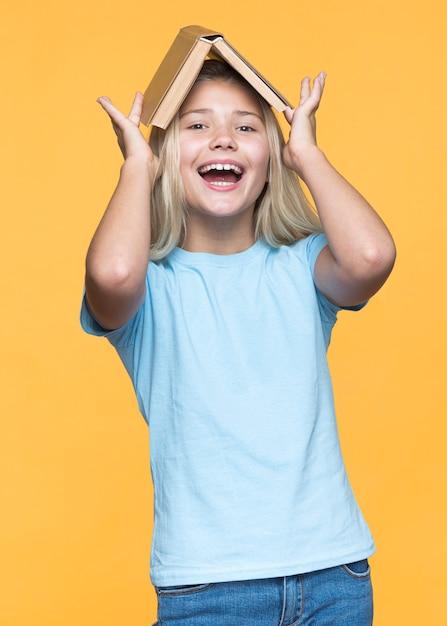 頭の上の本を保持している遊び心のある女の子 無料写真