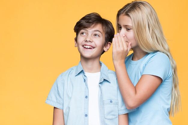 Сестра шепчет секрет младшему брату Бесплатные Фотографии