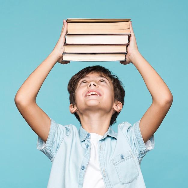 書籍のスタックを保持している遊び心のある少年 無料写真