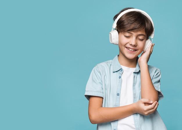 Молодой мальчик прослушивания музыки с копией пространства Бесплатные Фотографии