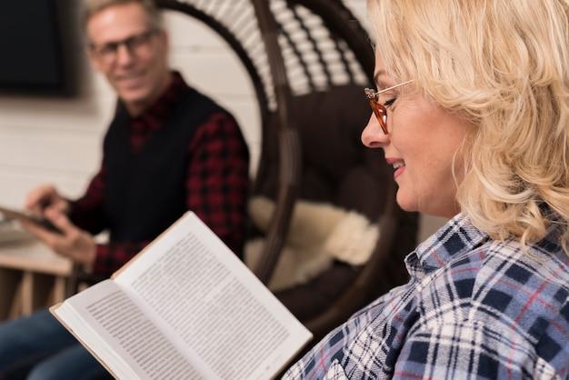 Взгляд со стороны матери читая книгу с расфокусированным отцом Бесплатные Фотографии