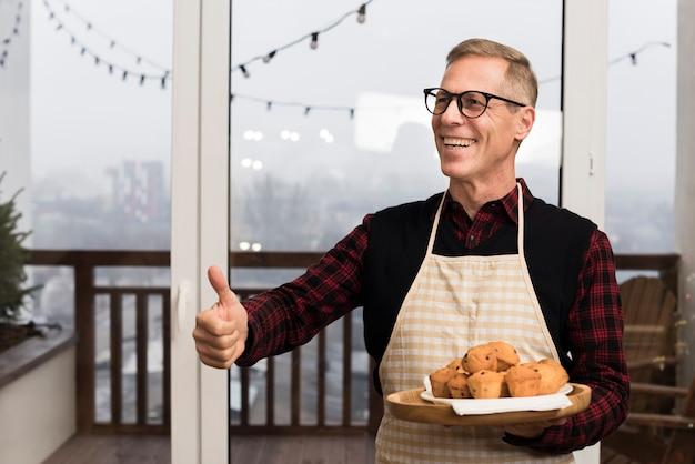 Счастливый отец дает большие пальцы, держа тарелку кексов Бесплатные Фотографии