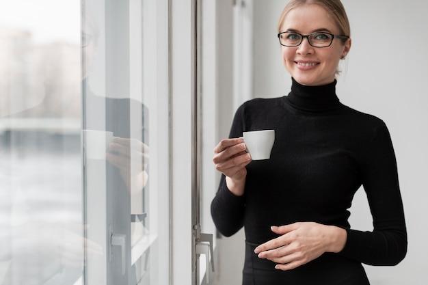 スマイリーの女性がコーヒーを飲む 無料写真