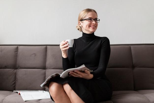 Женщина читает журнал и пьет кофе Бесплатные Фотографии