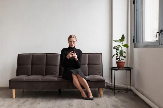 携帯電話を使用してソファの上の女性 無料写真