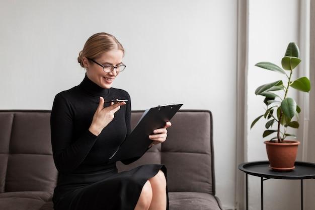 携帯電話とクリップボードを持つ女性 無料写真