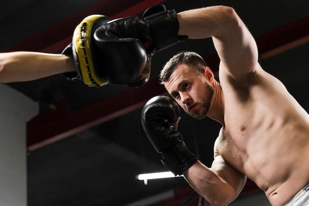 ハードトレーニングで助けを得る低角度の男 無料写真