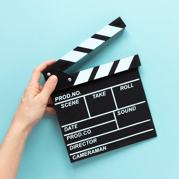 青の背景に映画クラッパーを持っている人 無料写真