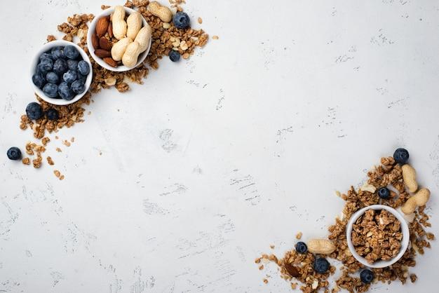 Вид сверху сухих завтраков в мисках с черникой и ассортиментом орехов Бесплатные Фотографии