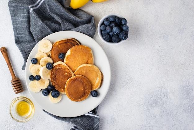 蜂蜜とブルーベリーのプレートに朝食のパンケーキのトップビュー 無料写真