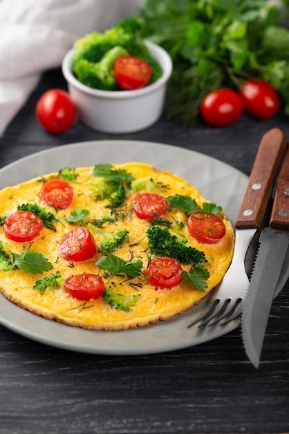 トマトとカトラリーと朝食のオムレツの高角 無料写真