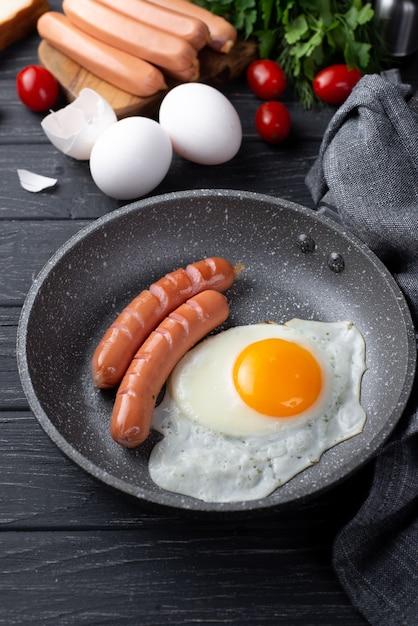朝食の卵とトマトとハーブの鍋にソーセージの高角 無料写真