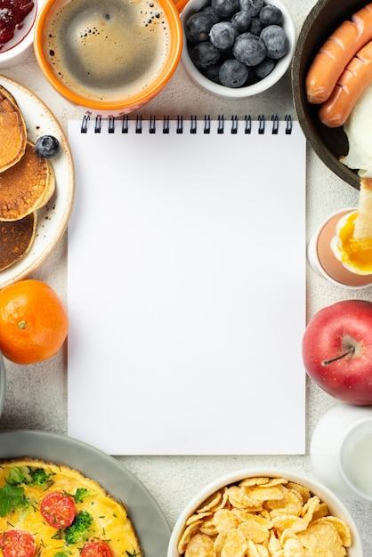 朝食用食品に囲まれたノートブックのトップビュー 無料写真