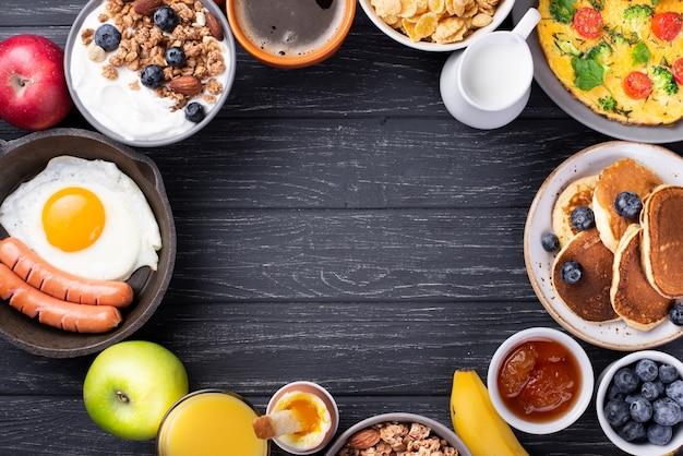 Вид сверху йогурта и хлопьев с яйцом и сосисками на завтрак Бесплатные Фотографии