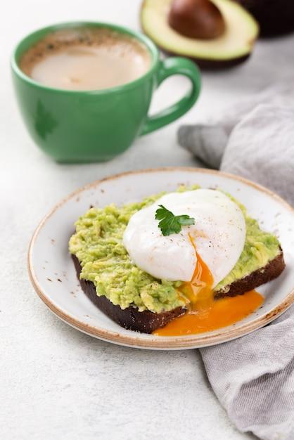 Тост из авокадо на тарелке с яйцом-пашот на вершине и кофейной чашкой Бесплатные Фотографии