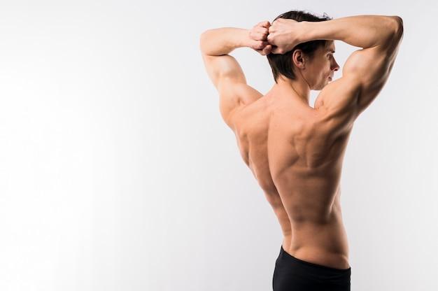 筋肉の体を披露して運動男の側面図 無料写真