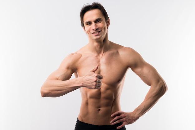 親指をあきらめながらポーズ筋肉質の男の正面図 無料写真