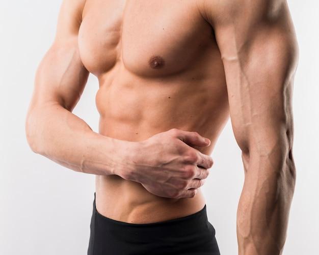 筋肉を披露して運動男の側面図 無料写真