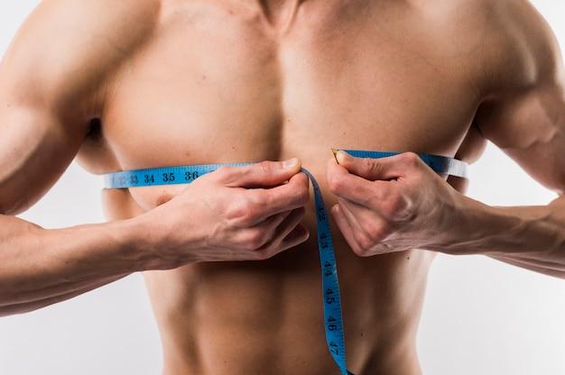 筋肉の胸を測定する男のクローズアップ 無料写真