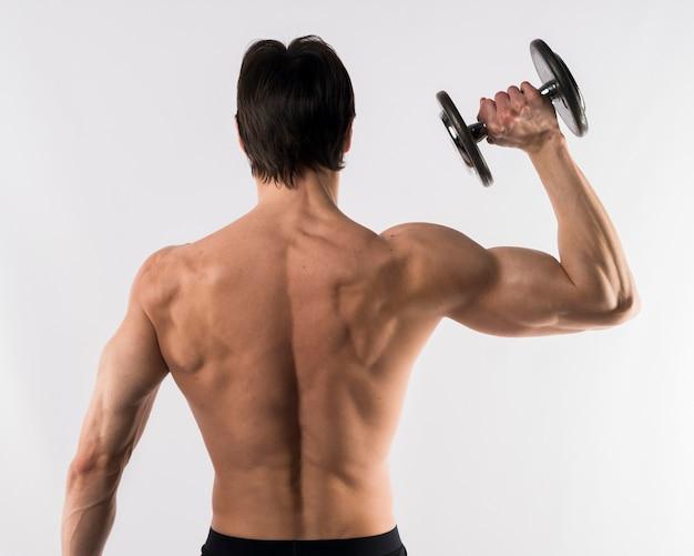 重量を保持しながら背中の筋肉を披露して上半身裸の運動男 無料写真
