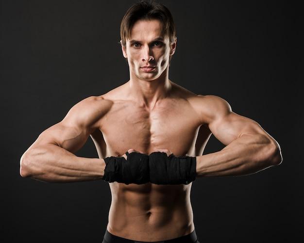 ボクシンググローブでポーズ筋肉の上半身裸の男の正面図 無料写真