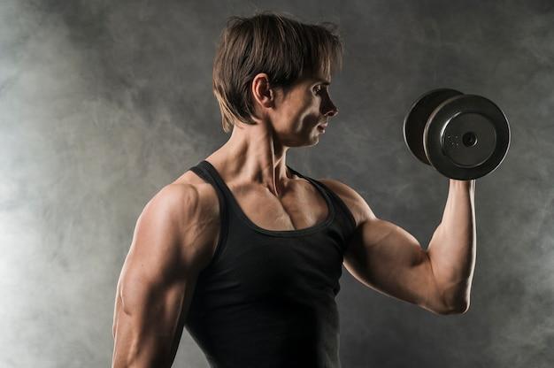 重量を保持している筋肉質の男の側面図 無料写真