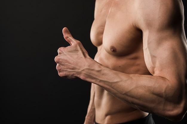 親指をあきらめて筋肉の上半身裸の男の側面図 無料写真