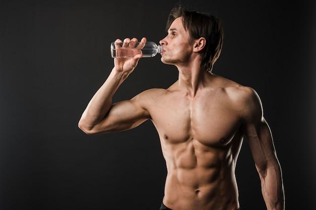 水を飲む運動の上半身裸の男の正面図 無料写真