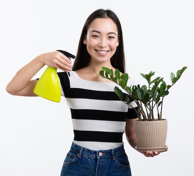 花を噴霧スマイリー女性を葉します。 無料写真