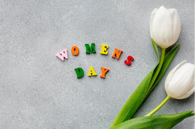 白いチューリップとセメントのトップビュー女性の日のレタリング 無料写真