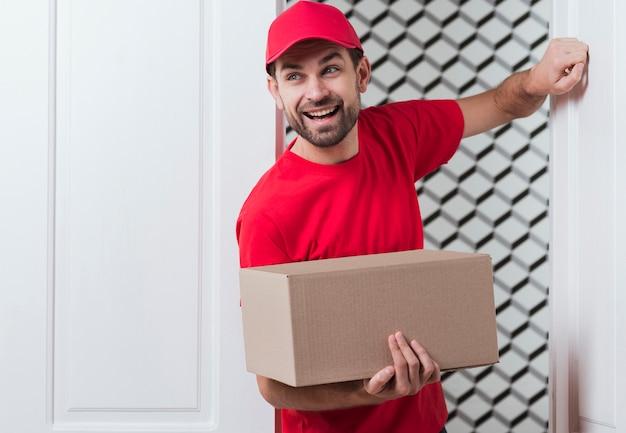 赤い制服を着て、ドアをノックして正面配達人 無料写真