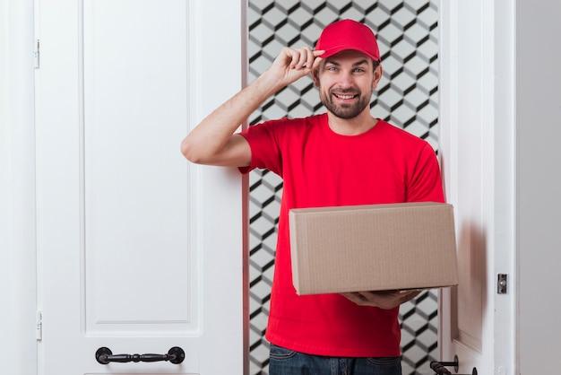 Курьер мужчина держит шапку и коробку Бесплатные Фотографии
