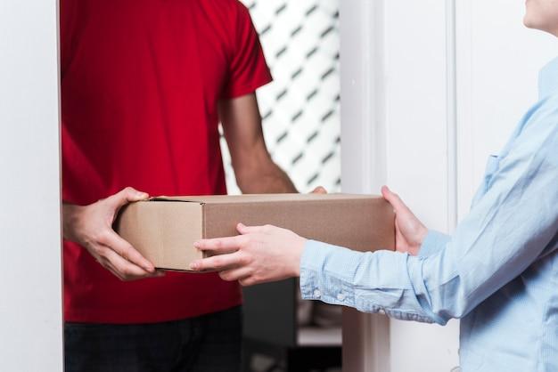 宅配便のクローズアップからパッケージを受け取る女性 無料写真