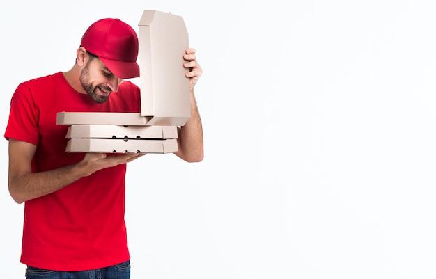 Доставка пиццы мальчик смотрит внутрь коробки Бесплатные Фотографии