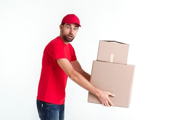 小包のポストボックスを保持しているサイドビュー配達少年 無料写真