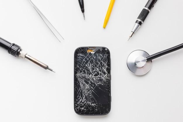 修理ツールで壊れたスマートフォンのトップビュー 無料写真