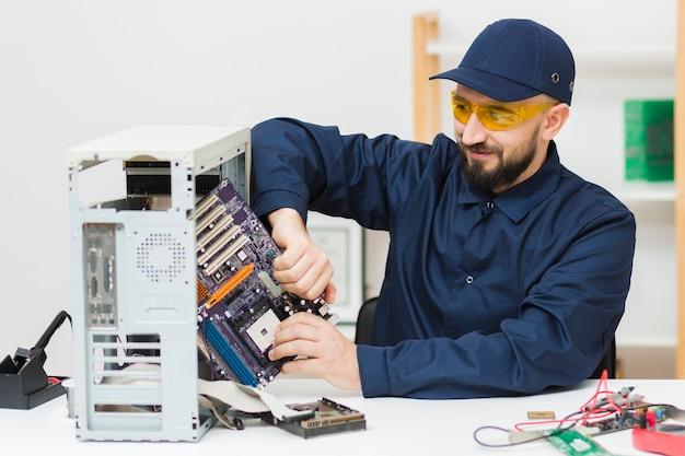 Вид спереди человек ремонтирует компьютер Бесплатные Фотографии