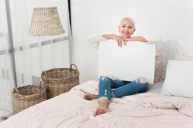 ベッドで空白のプラカードを保持しているスマイリー高齢女性 無料写真