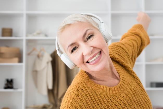 Улыбающаяся пожилая женщина наслаждается музыкой в наушниках Бесплатные Фотографии