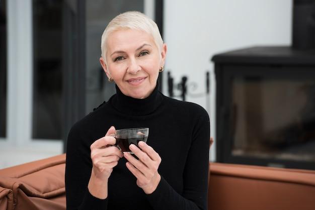 Вид спереди счастливой зрелой женщины позируют с чашкой кофе Бесплатные Фотографии