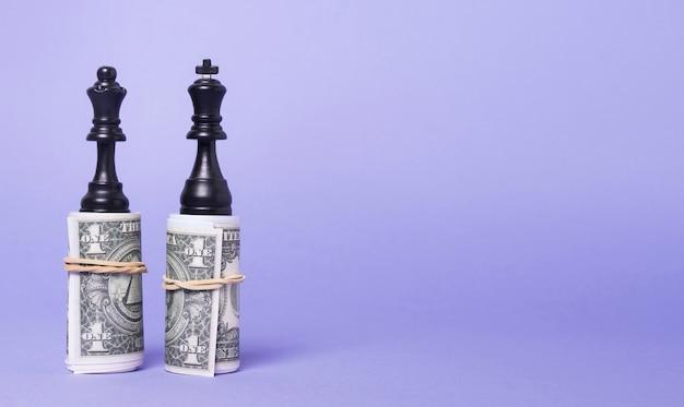 コピースペースでお金の上に立ってチェスの王と女王の作品 無料写真