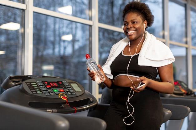Женщина высокого угла в спортзале используя чернь Бесплатные Фотографии