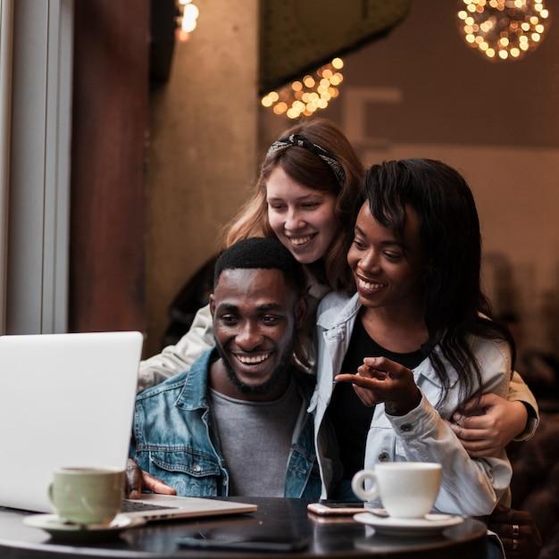 屋内でノートパソコンを見て幸せな友達 無料写真