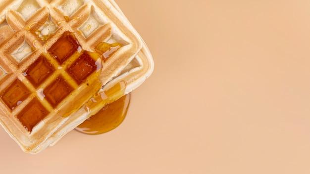 コピースペースでワッフルから滴る蜂蜜のトップビュー 無料写真