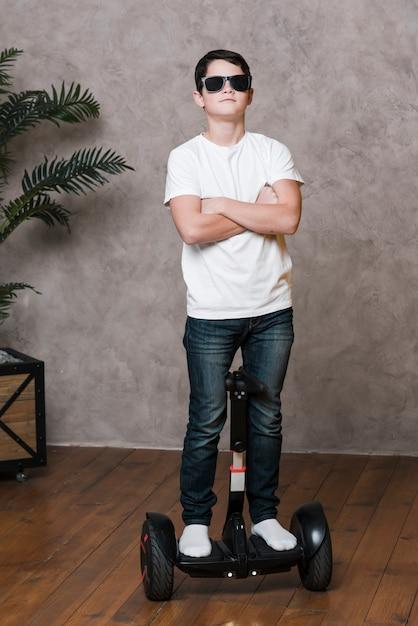 Полный снимок современного мальчика с очками на ховерборде Бесплатные Фотографии