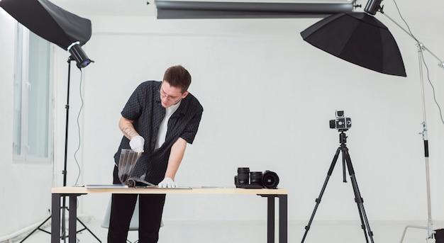 Человек в черной одежде работает в своей фотостудии Бесплатные Фотографии